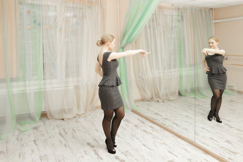 Femme dans la danse grise contre le miroir images stock