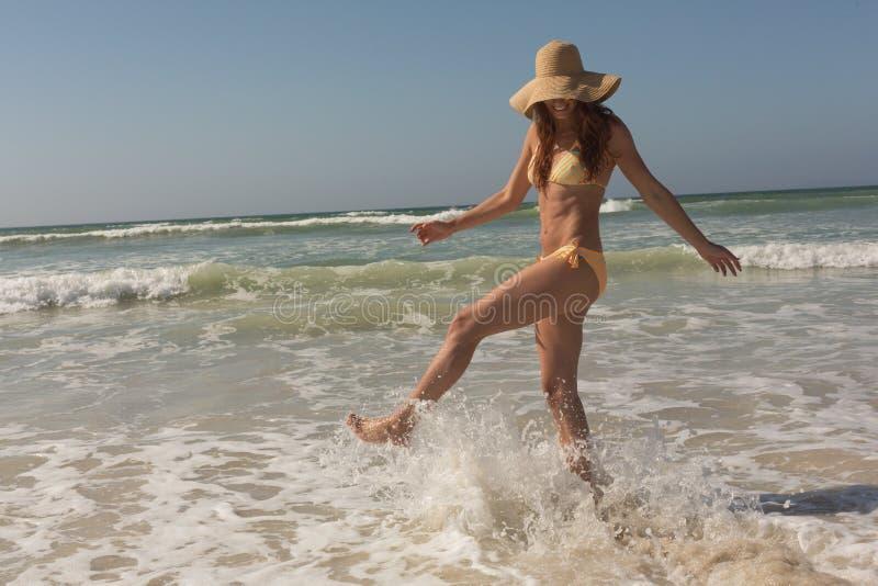 Jeune femme caucasienne dans le bikini et le chapeau donnant un coup de pied dans l'océan photographie stock