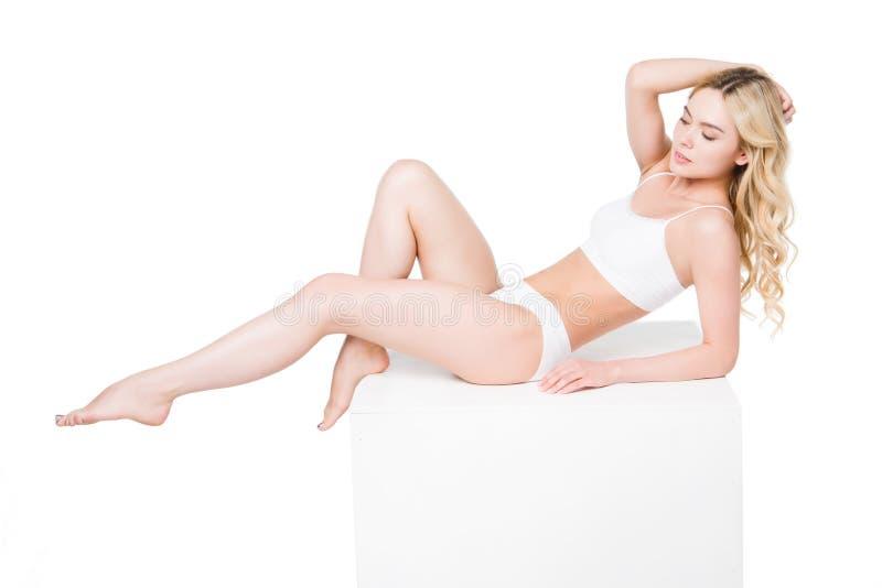 Jeune femme caucasienne dans les sous-vêtements blancs se trouvant sur la boîte photo libre de droits