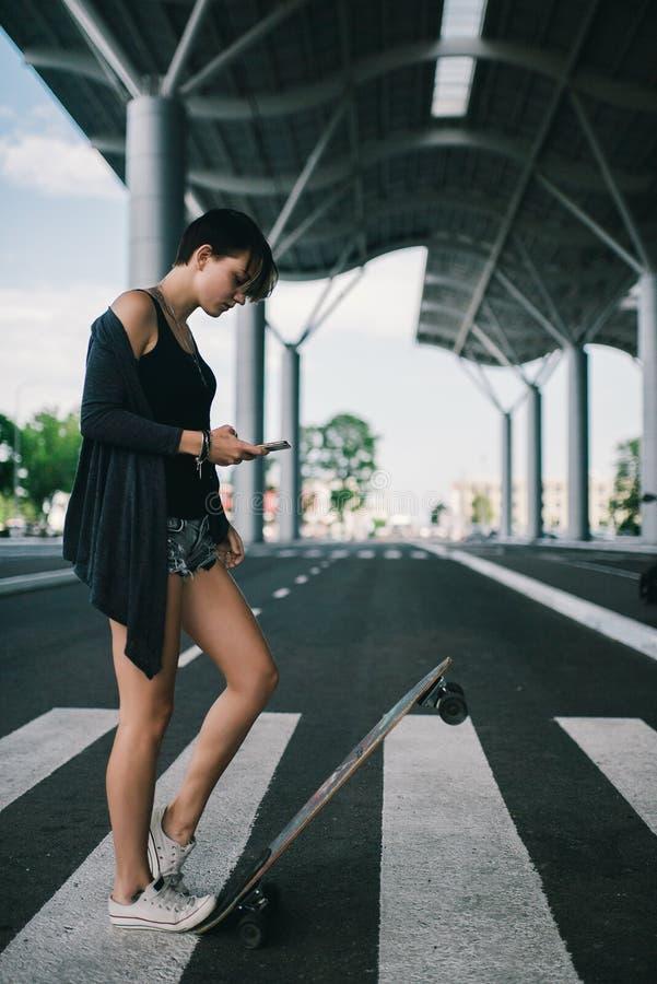 Jeune femme caucasienne de hippie avec une planche à roulettes de longboard sur la rue image stock