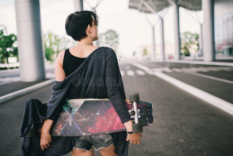 Jeune femme caucasienne de hippie avec une planche à roulettes de longboard sur la rue photographie stock