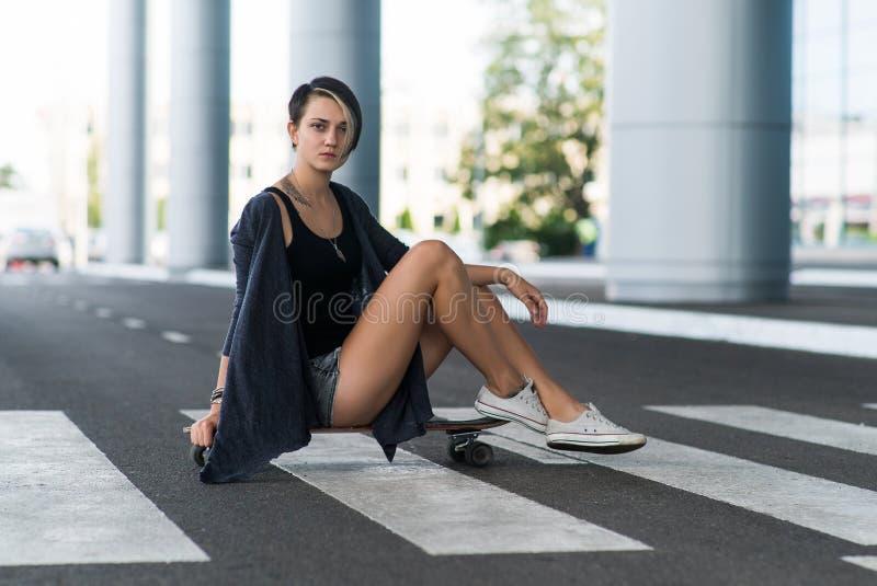 Jeune femme caucasienne de hippie avec une planche à roulettes de longboard sur la rue images libres de droits