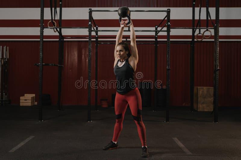 Jeune femme caucasienne de sports faisant l'exercice d'oscillation de kettlebell photos stock