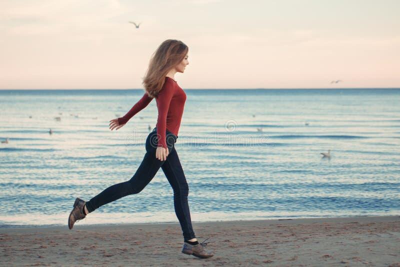 Jeune femme caucasienne enthousiaste riante de sourire dans des jeans courant sauter parmi des oiseaux de mouettes photographie stock libre de droits
