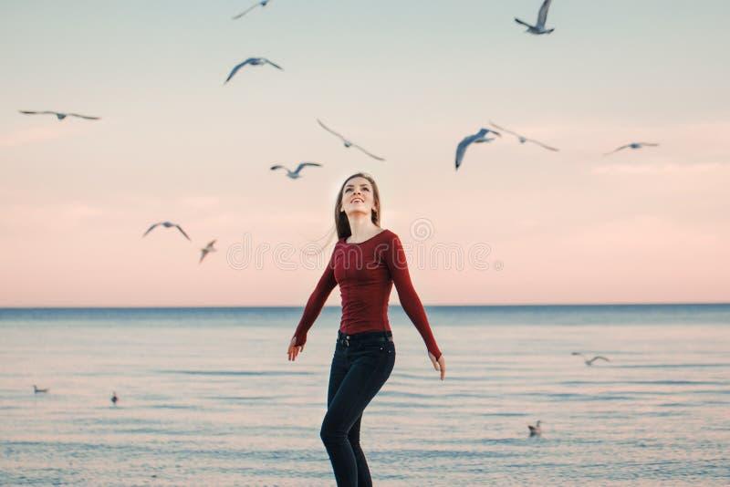 Jeune femme caucasienne enthousiaste riante de sourire dans des jeans courant sauter parmi des oiseaux de mouettes images stock