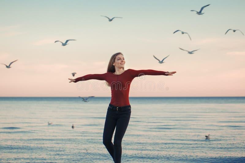Jeune femme caucasienne enthousiaste riante de sourire dans des jeans courant sauter parmi des oiseaux de mouettes image stock