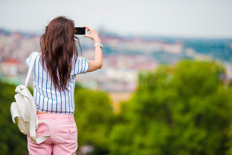 Jeune femme caucasienne faisant la photo de la vieille ville européenne par le téléphone portable à partir de l'endroit d'observa photographie stock