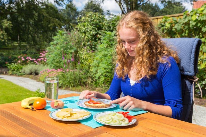 Jeune femme caucasienne mangeant le petit déjeuner dans le jardin photos stock