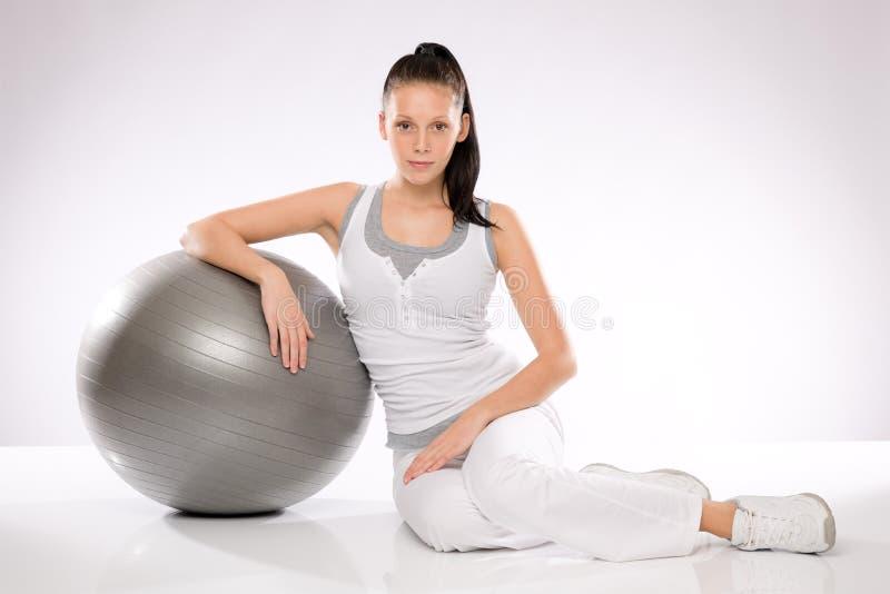Jeune femme caucasienne se penchant sur la bille de forme physique photo stock