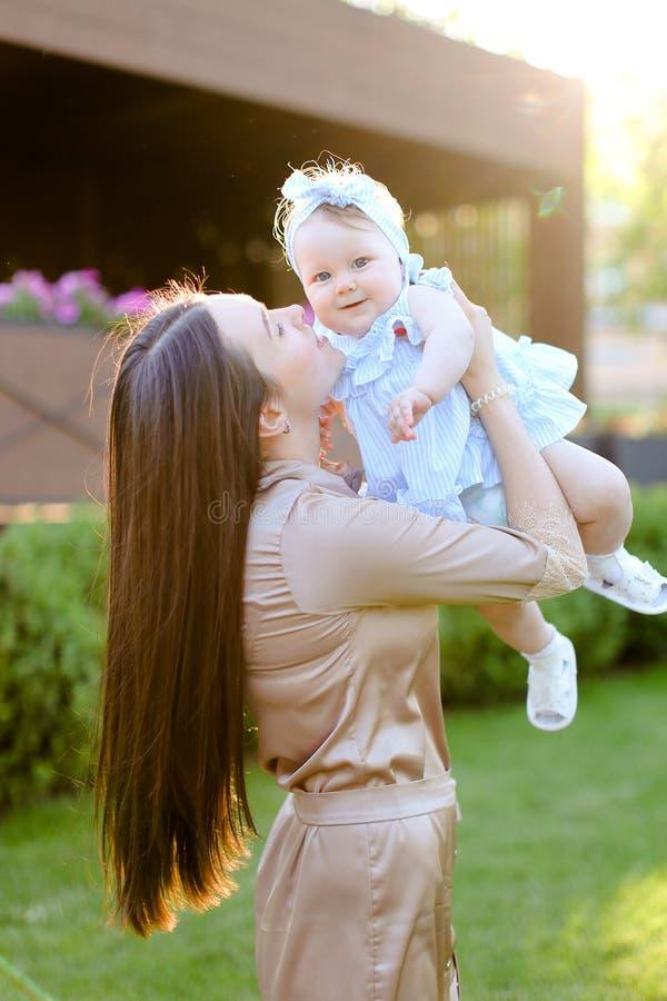Jeune femme caucasienne tenant et embrassant peu de fille images stock