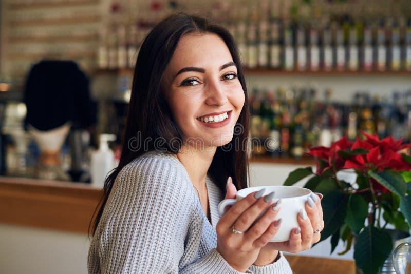 Jeune femme caucasienne tenant la tasse de café au café image stock