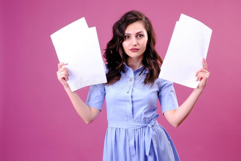Jeune femme caucasienne tenant le papier au-dessus du fond rose effray? dans le choc avec un visage de surprise, effray? et excit photographie stock libre de droits