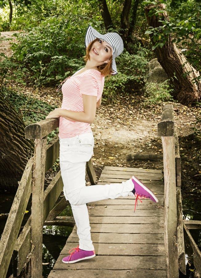 Jeune femme cauciasian avec le chapeau de soleil posant sur le pont en bois photographie stock libre de droits