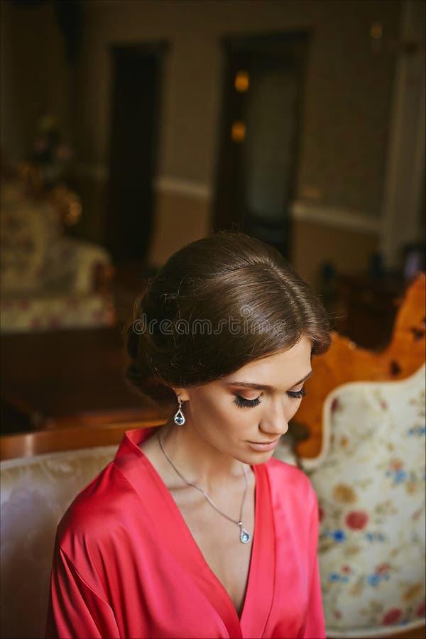 Jeune femme châtain très belle avec le maquillage doux et avec de longs cils dans un peignoir rose et en bijoux images stock