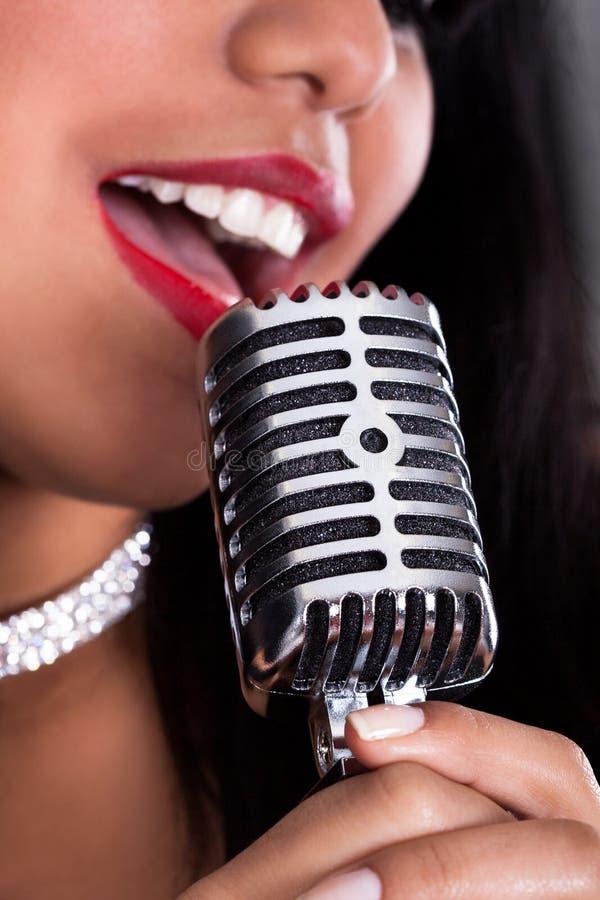 Jeune femme chantant dans le microphone image stock