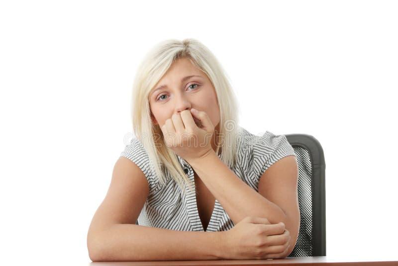 Jeune femme chargée s'asseyant derrière un bureau photographie stock libre de droits