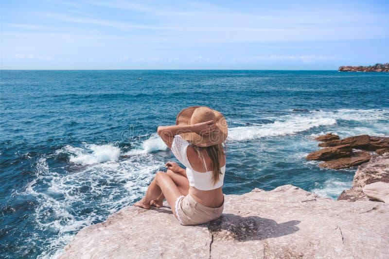 Jeune femme chic s'asseyant par l'océan photo stock