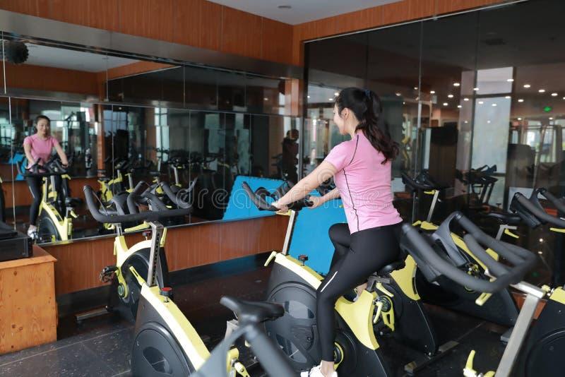 Jeune femme chinoise asiatique de forme physique sur la rotation de vélo de gymnase image libre de droits