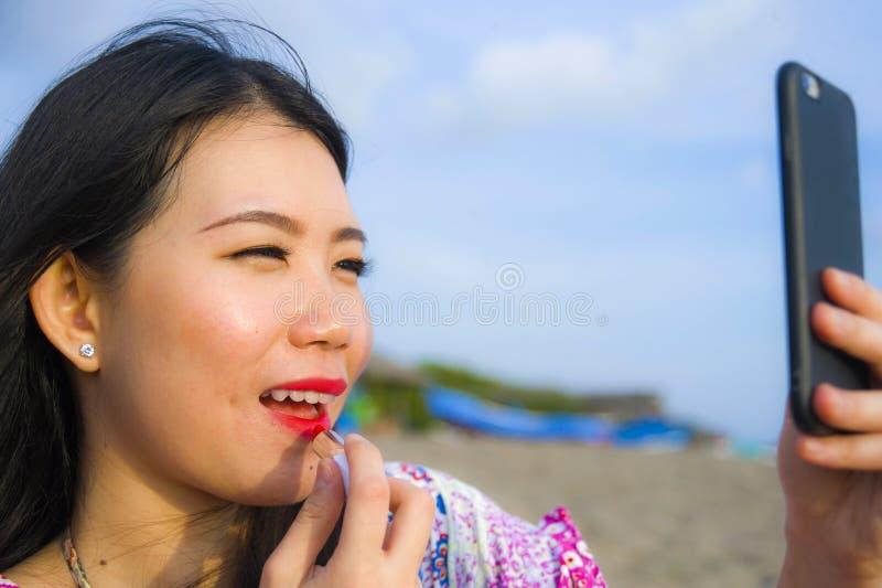 Jeune femme chinoise asiatique heureuse et belle retouchant son maquillage appliquant le rouge à lèvres rouge sur ses lèvres util photo libre de droits