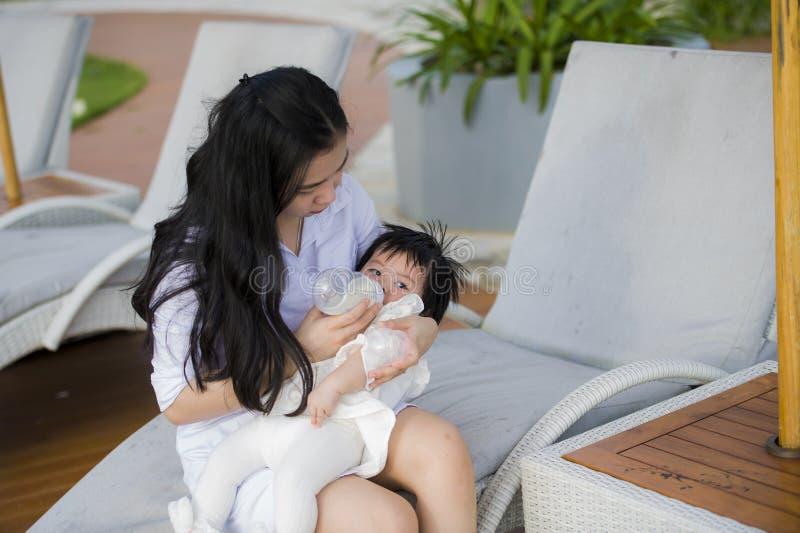 Jeune femme chinoise asiatique heureuse et mignonne jouant avec le bébé de fille à la piscine tropicale de station de vacances de image stock