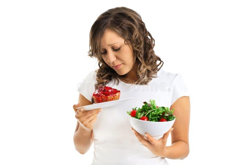 Jeune femme choisissant des bonbons ou la consommation saine image stock