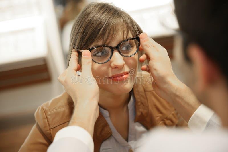 Jeune femme choisissant des lunettes photographie stock libre de droits