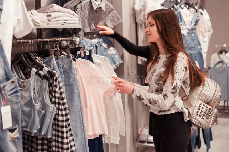 Jeune femme choisissant des vêtements sur un support dans une salle d'exposition photographie stock