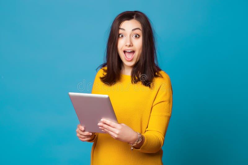 Jeune femme choquée à l'aide du comprimé photos stock