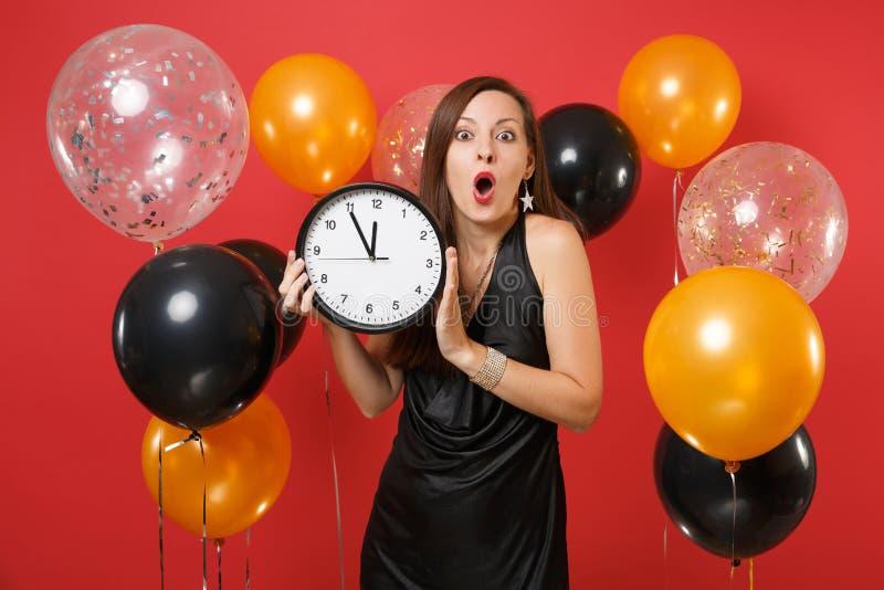Jeune femme choquée dans la robe noire célébrant tenant l'horloge ronde sur le ballon à air rouge de fond Le temps s'épuise photo stock
