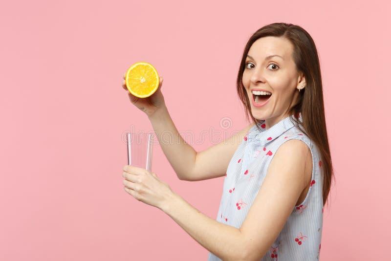 Jeune femme choquée enthousiaste dans des vêtements d'été se tenant à moitié de la tasse en verre de fruit orange mûr frais d'iso images libres de droits