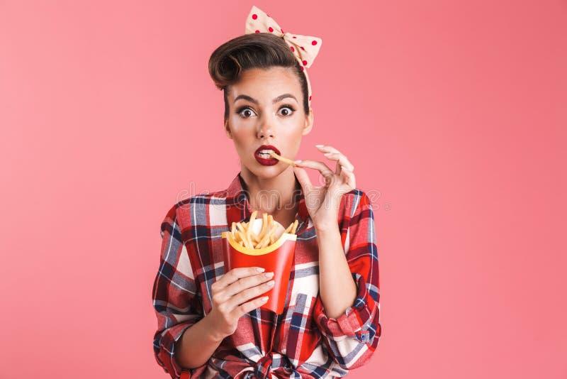 Jeune femme choquée enthousiaste de goupille- tenant des pommes frites image stock