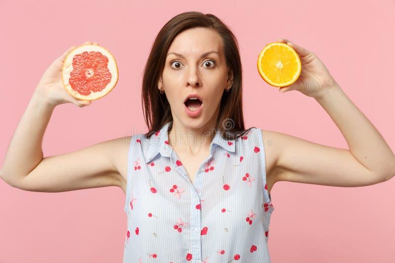Jeune femme choquée gardant les halfs se tenants ouverts de bouche du pamplemousse mûr frais, fruit orange d'isolement sur le mur images libres de droits