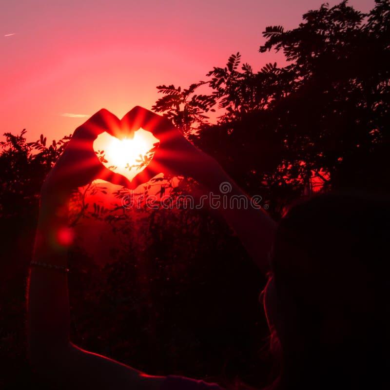 Jeune femme, coeur et coucher du soleil photo stock