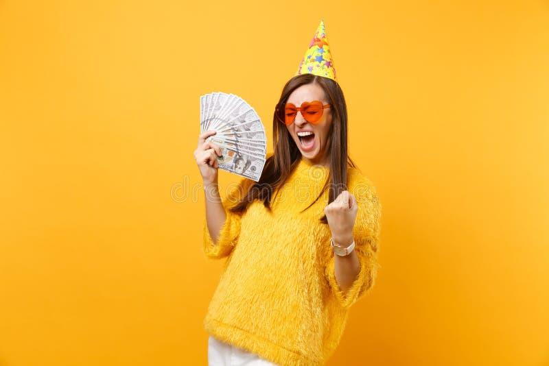 Jeune femme comblée dans le chapeau orange d'anniversaire en verre de coeur faisant le geste de gagnant, dire oui tenant beaucoup photos libres de droits