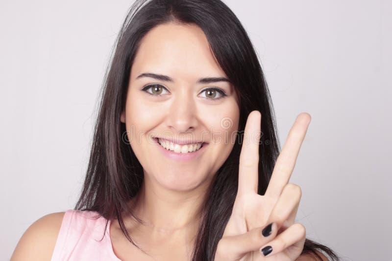 Jeune femme comptant deux avec ses doigts images stock