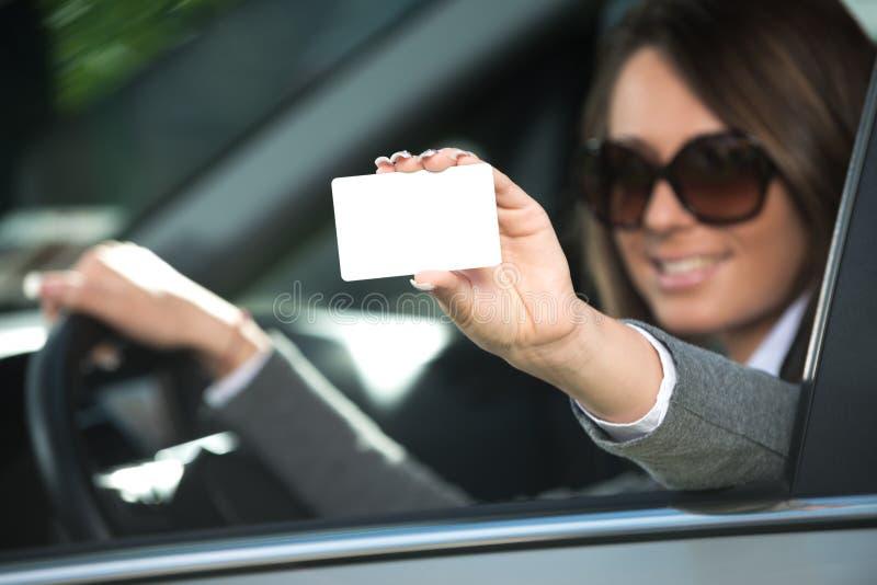 Jeune femme conduisant et tenant la carte de visite professionnelle de visite image stock