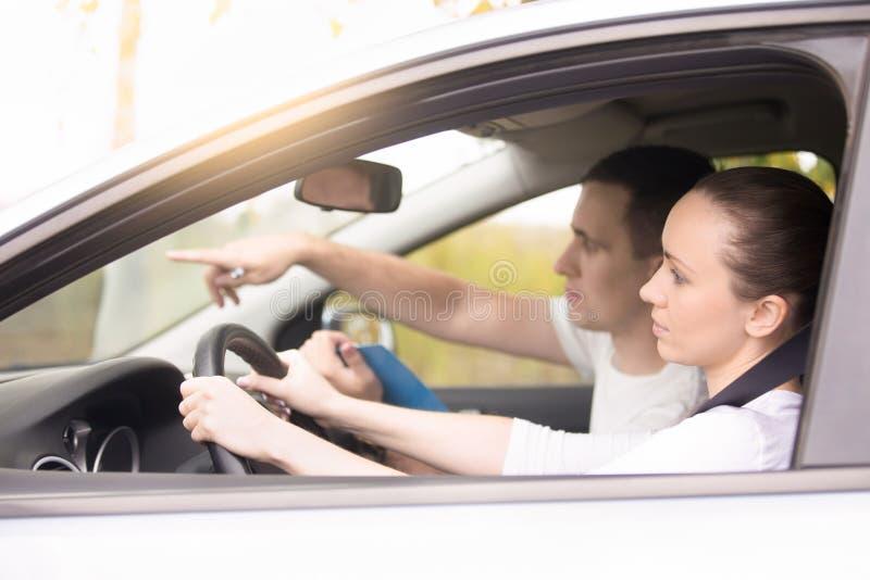 Jeune femme conduisant, homme dirigeant la direction photo stock