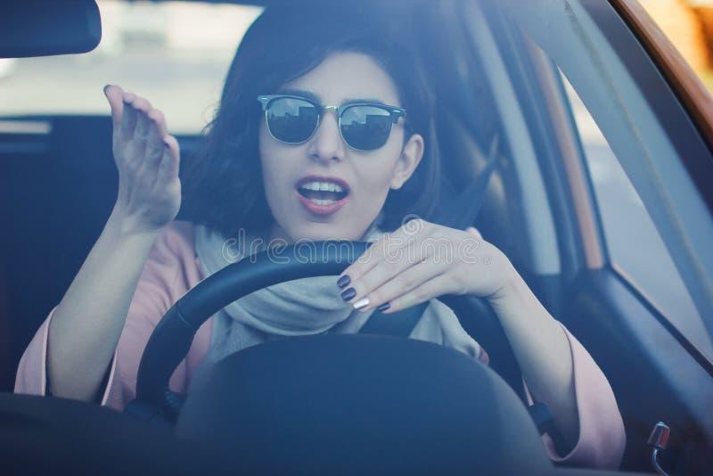 Jeune femme conduisant son véhicule photographie stock