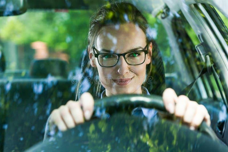 Jeune femme conduisant un véhicule photographie stock