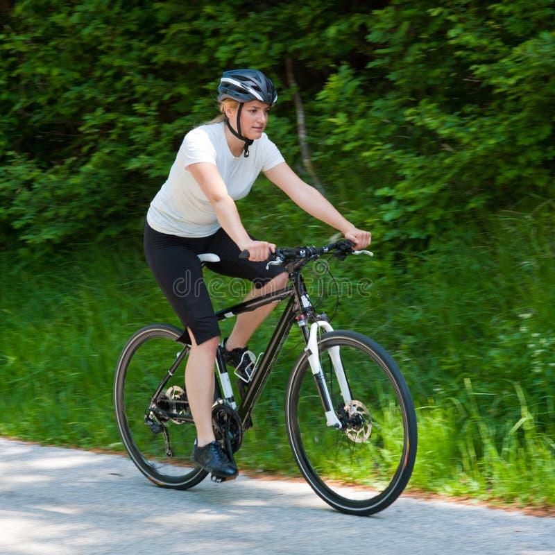 Jeune femme conduisant un vélo sur la route par la forêt photos libres de droits