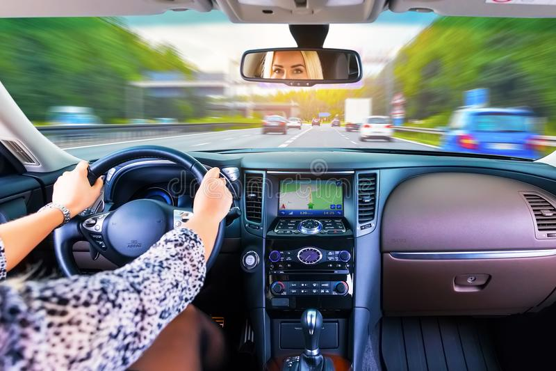 Jeune femme conduisant une voiture sur une route photos stock