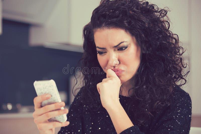 Jeune femme confuse bouleversée regardant le message textuel de lecture de téléphone portable photographie stock libre de droits