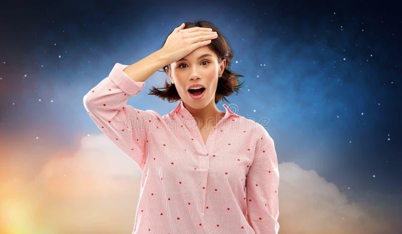 Jeune femme confuse dans le pyjama au-dessus du ciel nocturne photographie stock