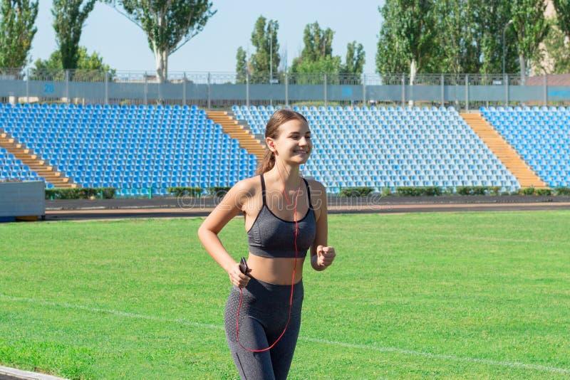 Jeune femme convenable écoutant la musique et le fonctionnement sur la voie de stade Sports et concept sain photo stock