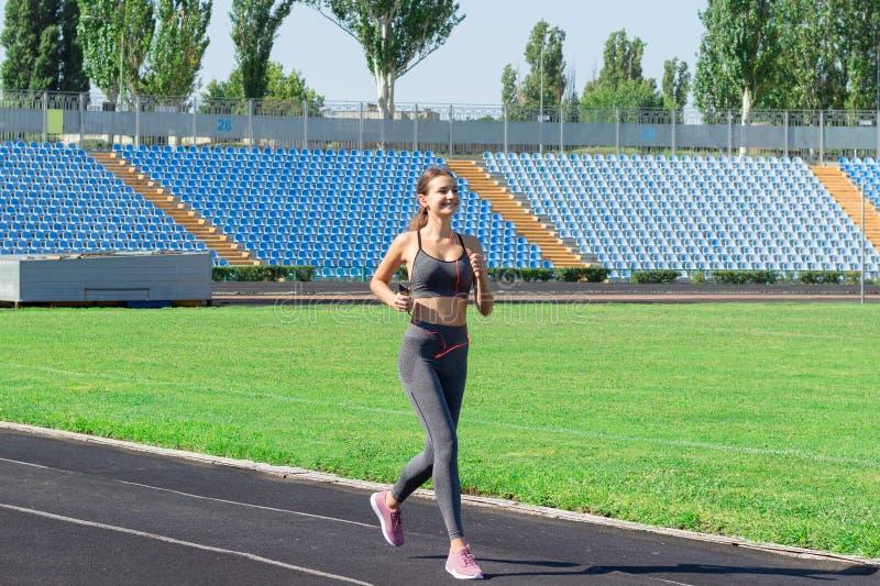 Jeune femme convenable écoutant la musique et le fonctionnement sur la voie de stade Sports et concept sain images stock