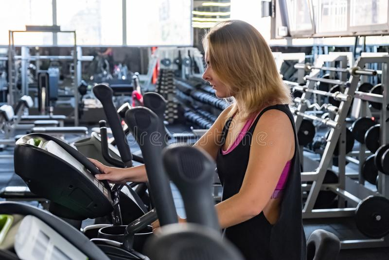 Jeune femme convenable au gymnase utilisant l'entraîneur croisé elliptique Femal photographie stock libre de droits