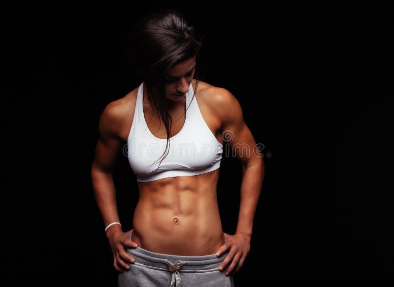 Jeune femme convenable dans les vêtements de sport regardant vers le bas photos stock