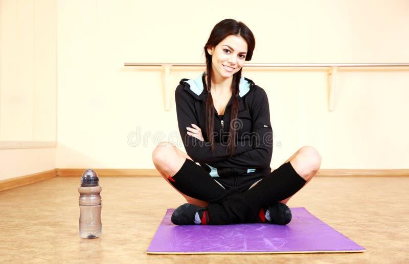 Jeune femme convenable de sourire s'asseyant sur le tapis de yoga photos libres de droits