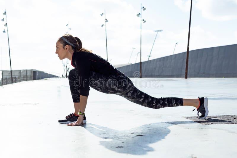 Jeune femme convenable et sportive faisant l'étirage dans la ville photos stock