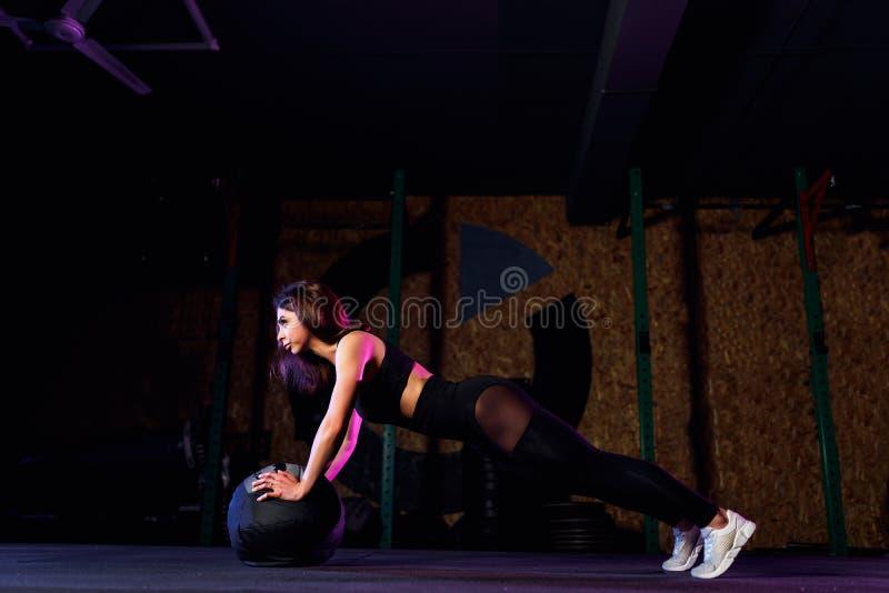 Jeune femme convenable faisant la poussée ou l'exercice de planche sur le medicine-ball au gymnase photos libres de droits